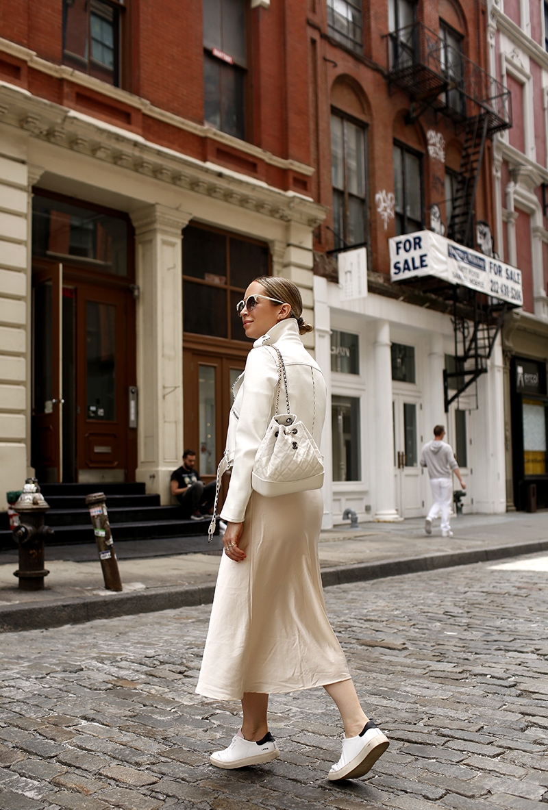 White Leather Biker Jacket, Beige Slip Dress, Axel Arigato White Sneakers, Chanel White Quilted Backpack, Spring Summer Maternity Outfit Idea, Helena of Brooklyn Blonde