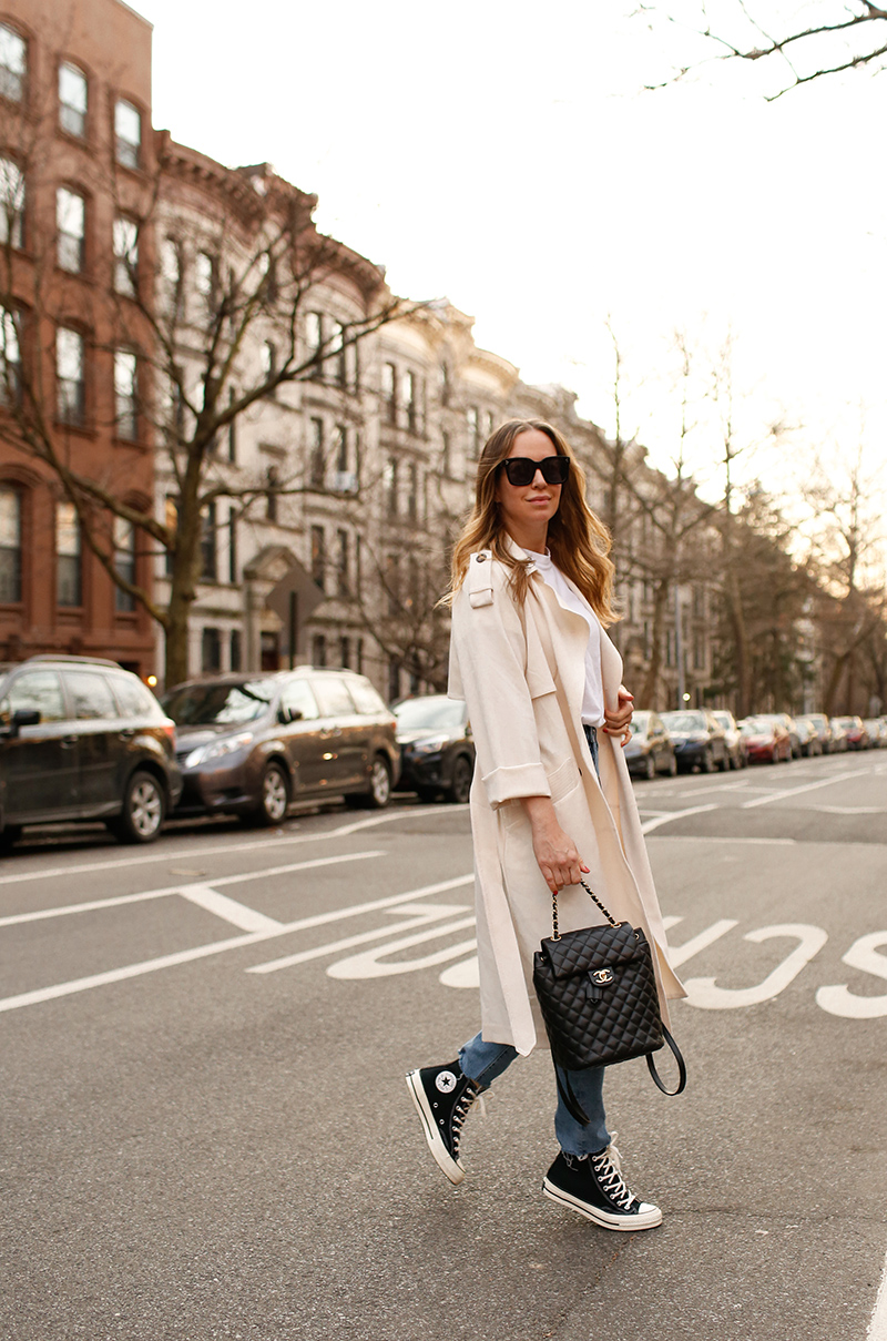 woman walking on the street wearing Trench Coats with Converse