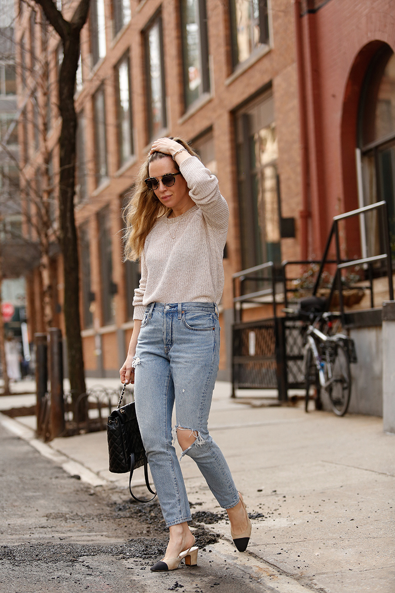 woman wearing her favorite Pairs of Denim, a sweater, and touching her hair