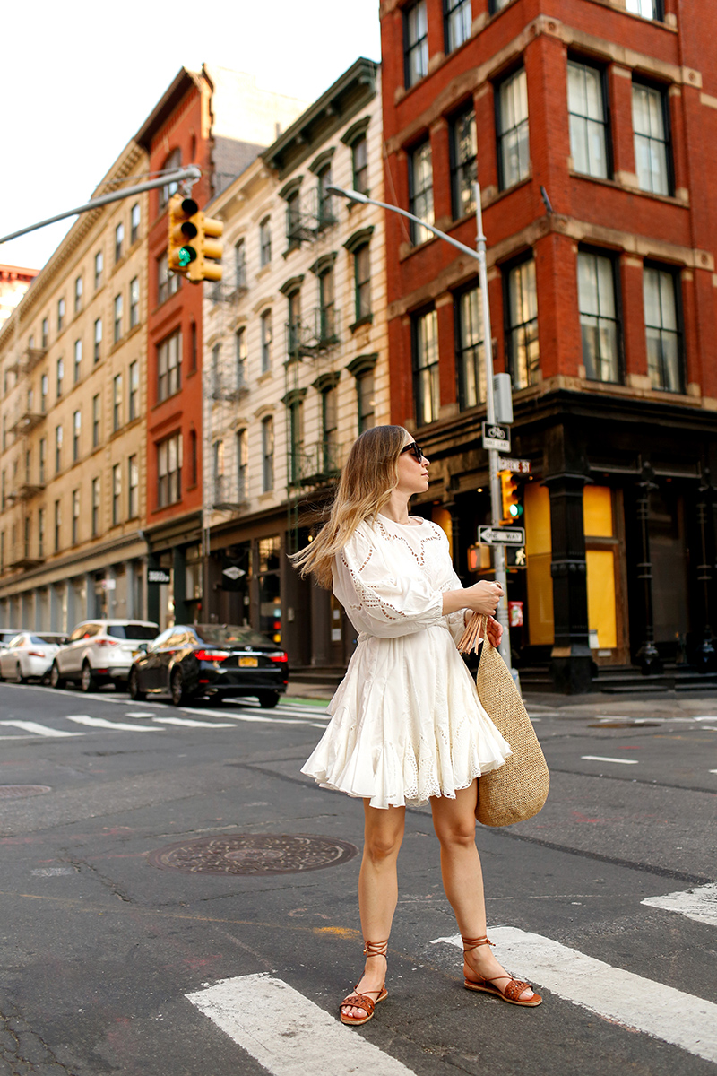 woman walking on the streets and wearing white dress for Summer Shopbop Picks