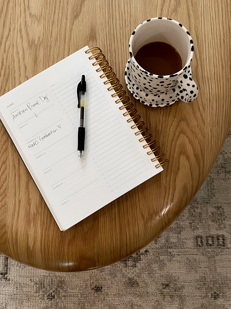 open notebook written on it s Amazon Prime Sale and a coffee mug on a table for